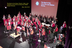 The Band receiving applause, on stage at the Roper Theatre, Bath, with the Devon & Somerset Corps of Drums in background.